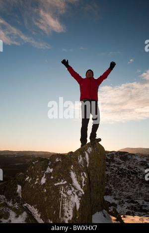 L'alpiniste sur Todd Crag summit dans le Lake District, UK, au crépuscule. Banque D'Images