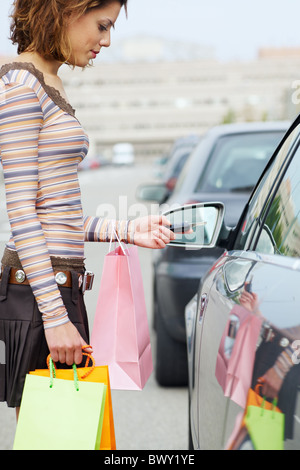 Woman with shopping bags holding car keys Banque D'Images