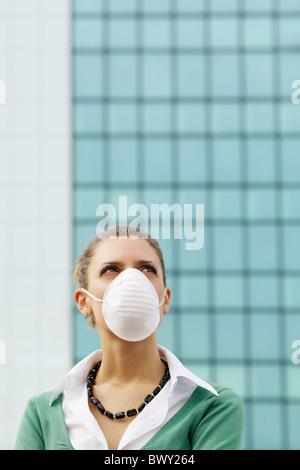 Femme debout contre l'immeuble de bureaux et le port de masque de protection. Copy space Banque D'Images