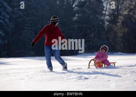 Femme fille enfant tirant sur le traîneau en bois en hiver paysage, Dobel, Forêt Noire, Allemagne Banque D'Images