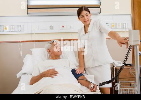 Infirmière en tenant la pression artérielle du patient in hospital room Banque D'Images