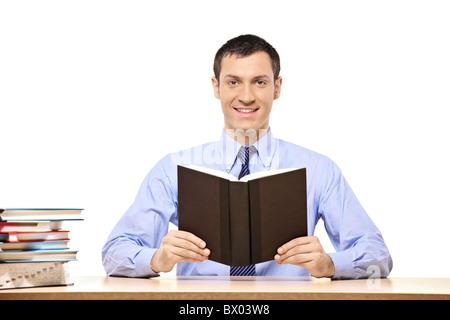 Un étudiant de lire un livre, avec beaucoup d'autres livres sur le bureau Banque D'Images