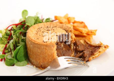 Un steak pie, servi avec des chips de pomme de terre frites et une salade verte. Banque D'Images