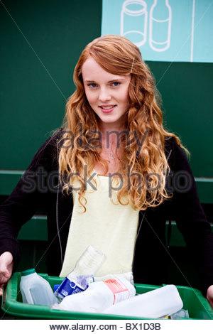 Une jeune fille tenant un récipient pour recyclage Banque D'Images