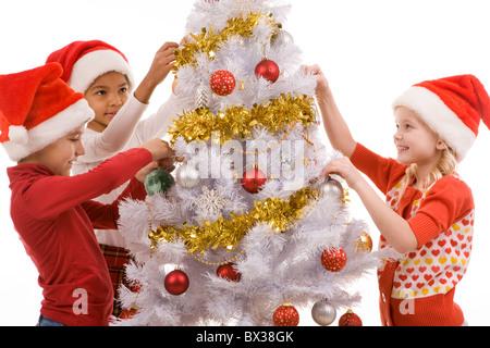 Groupe d'enfants par le Nouvel An des arbres le décorer avec des guirlandes et des boules de jouet d'or Banque D'Images