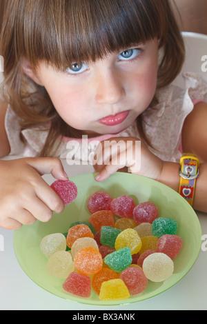 Gourmand à deux ans, fille de manger un bol de bonbons Banque D'Images