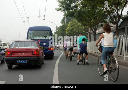 Les voitures et les vélos en concurrence pour l'espace sur une route pendant un embouteillage à Pékin, en Chine. Banque D'Images