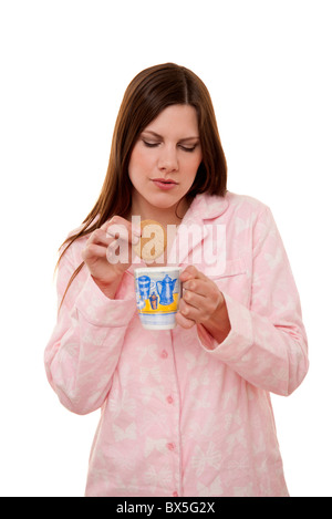 Tremper un biscuit dans femme une tasse de thé Banque D'Images
