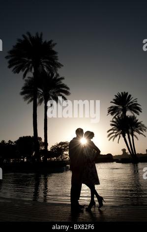Un jeune couple est découpé sur le coucher de soleil au bord d'une piscine en Egypte avec de superbes palmiers dans Banque D'Images