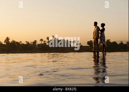 Un jeune couple est perchée sur le bord d'une piscine au coucher du soleil avec le Nil et de palmiers à l'arrière Banque D'Images