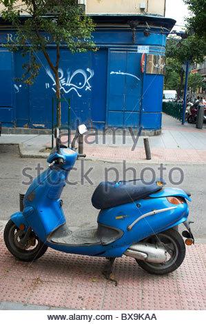 Scooter bleu stationné près d'un bâtiment bleu à Madrid en Espagne