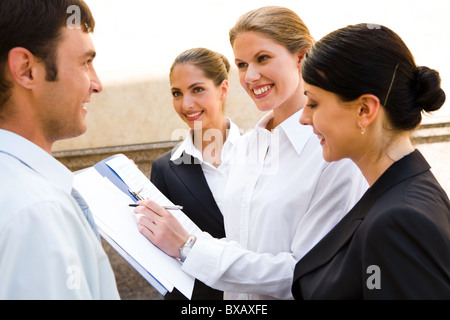 Équipe de jeunes professionnels souriante discutent de nouvelles idées d'affaires d'un bâtiment d'arrière-plan Banque D'Images