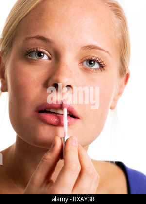 Young woman applying lip gloss, close-up Banque D'Images