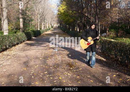 Homme espagnol qui joue de la guitare tout en marchant à travers le Parque de El Retiro Madrid Espagne. Photo:Jeff Banque D'Images