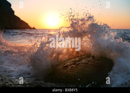 Au lever du soleil, les vagues déferlent sur la pierre Banque D'Images