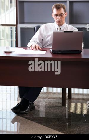 Smart businessman confortablement installé à la table à travailler sur son ordinateur portable au bureau Banque D'Images