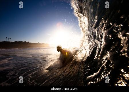 Un surfeur mâle tire dans un tonneau à Zuma beach à Malibu, en Californie. Banque D'Images