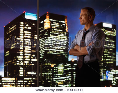 Serious businessman looking out glass wall at night cityscape Banque D'Images