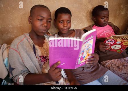 Les adolescentes lire ensemble à un programme après l'école en Iringa, Tanzanie, Afrique de l'Est. Banque D'Images