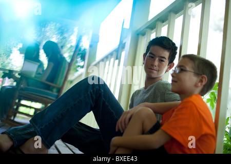 Deux jeunes garçons assis sur le porche Banque D'Images