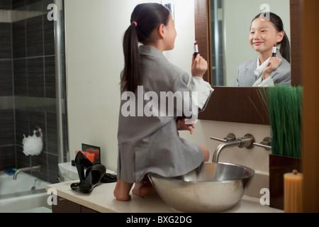 Mixed Race girl sur la lutte contre la mise sur le rouge à lèvres Banque D'Images