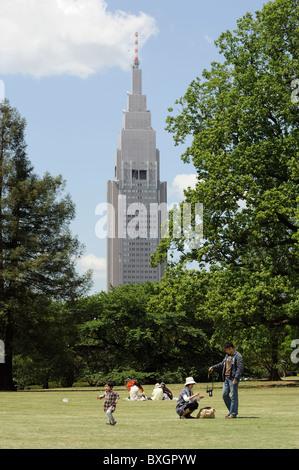 Famille japonaise à Shinjuku Park Tower DoCoMo avec en arrière-plan, Tokyo, Japon Banque D'Images