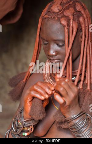 Femme Himba dans sa hutte styling sa coiffure dans un village près d'Epupa Falls, la Namibie, l'Afrique.