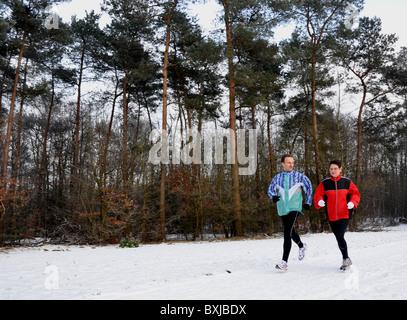 Jeune homme et femme senior en marche dans la neige Banque D'Images