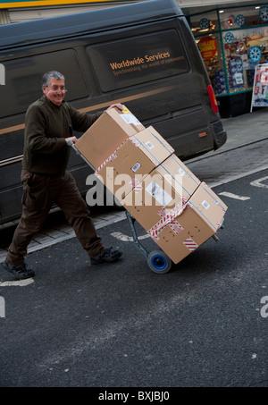 Un UPS United Messagerie service de messagerie, l'homme fournissant une pile de colis à un client, UK Banque D'Images