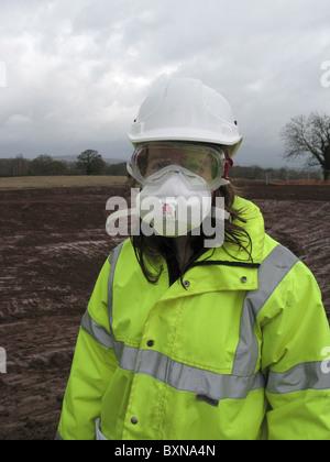 Jeune femme ingénieur civil portant un équipement de protection complet contre la chaux sur UK site de construction. Banque D'Images