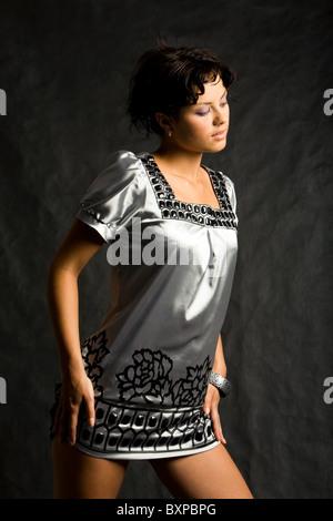 Portrait de femme élégante portant robe grise et à côté sur fond noir Banque D'Images
