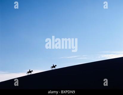 Les cavaliers au crépuscule sur une dune de sable dans la Valle De La Muerte dans les montagnes de la Cordillère Banque D'Images
