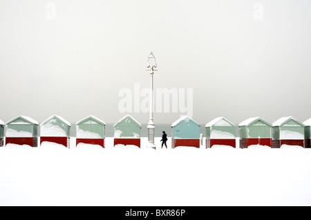 Un marcheur passe une rangée de cabanes de plage couverte de neige Banque D'Images