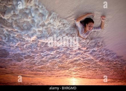Young woman lying in surfez sur la plage au coucher du soleil Banque D'Images