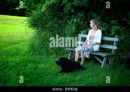 Femme assise sur un banc de travail avec chien labrador noir à côté Banque D'Images