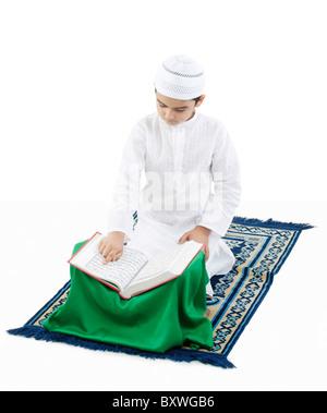 Garçon musulman lire le Coran Banque D'Images