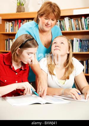 Aide bibliothécaire deux étudiants adolescents avec leur recherche. Banque D'Images