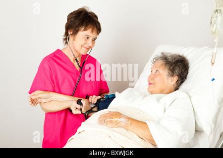 L'infirmière prend une haute pression artérielle du patient à l'hôpital. Banque D'Images