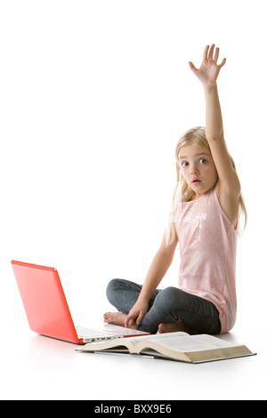 Cute little girl s'asseoir avec l'ordinateur portable et levant la main livre isolé sur fond blanc Banque D'Images