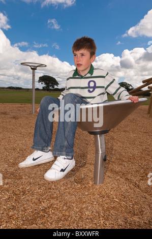 Un modèle photo parution d'un garçon de onze ans dans une pièce de Park au Royaume-Uni Banque D'Images