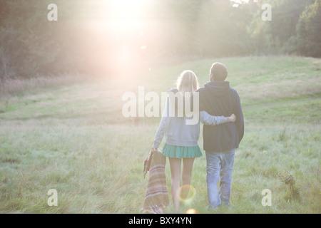 Vue arrière d'un jeune couple en train de marcher dans la campagne