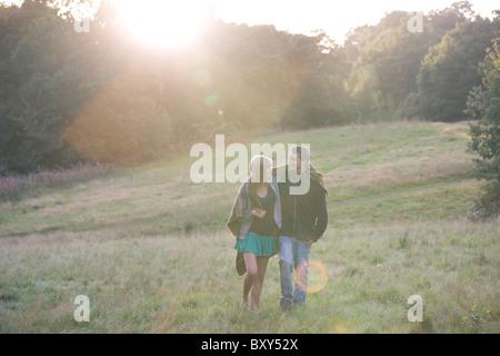 Un jeune couple en train de marcher dans la campagne sous le soleil du soir