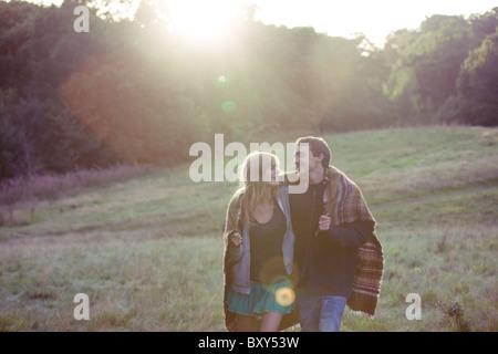 Un jeune couple en train de marcher dans la campagne, rire