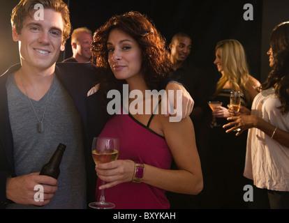Portrait de couple embracing at nightclub Banque D'Images