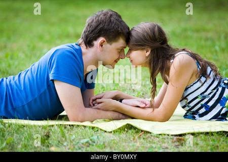 Photo de jolie fille et beau mec allongé sur l'herbe verte en face de l'autre et touchant l'un un autre visage et Banque D'Images