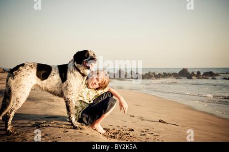 Portrait d'un jeune garçon et son chien au coucher du soleil sur une plage tranquille au Mexique. Banque D'Images