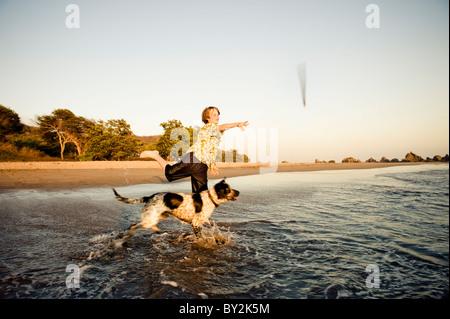 Un jeune garçon joue fetch avec son chien, au coucher du soleil sur une plage au Mexique. Banque D'Images