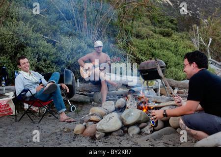 Trois amis s'asseoir autour d'un feu de camp à Rincon Beach State Park près de Carpinteria, en Californie. Banque D'Images