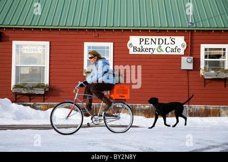 Une femme vélos avec son chien dans l'hiver à travers la ville de Driggs Texas après un arrêt à une petite boulangerie Banque D'Images