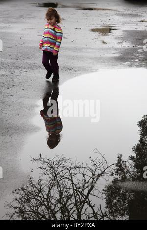 Une fillette de 3 ans à marcher le long du bord d'une flaque d'eau, avec des branches d'arbre. Banque D'Images